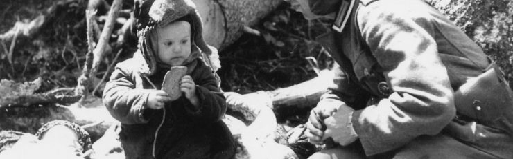 German soldier giving bread to an orphaned Russian boy. Volkhov area, 1942